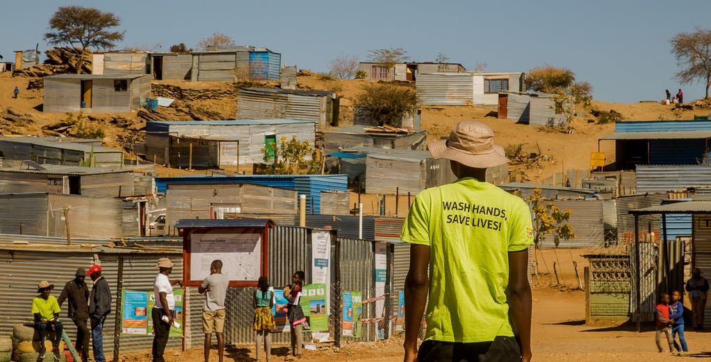 A volunteer wearing a t-shirt that says - Wash hands, save lives - approaches an informal settlement.