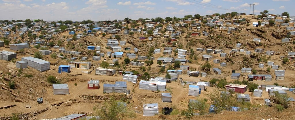 MAny shacks scattered across a sandy valley.