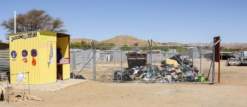 A yellow building next to a fenced area with a piles of refuse within it.
