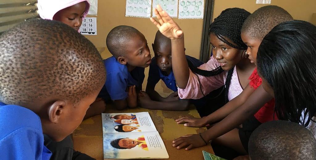 A goup of young children listen intently to their teacher.