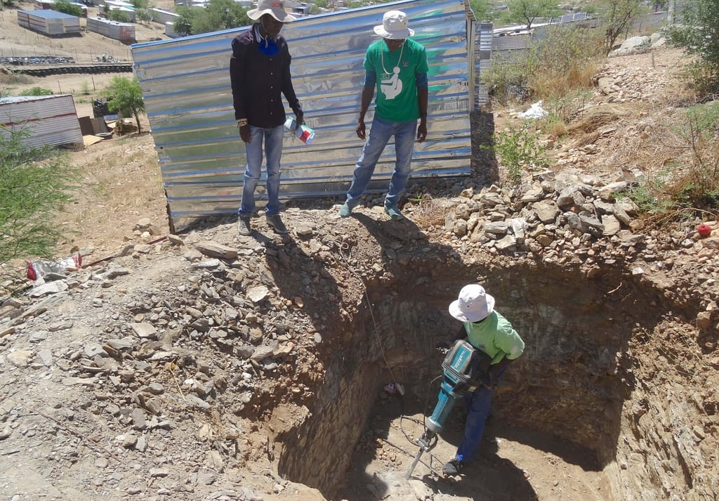Two men watch as a third operates a drill in an earthen pit.